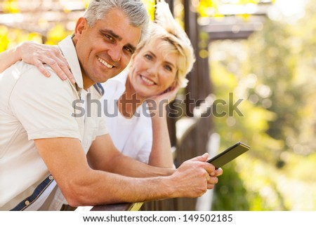 loving senior couple with tablet computer outdoors - stock photo