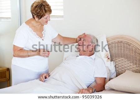 loving senior wife comforting ill husband - stock photo