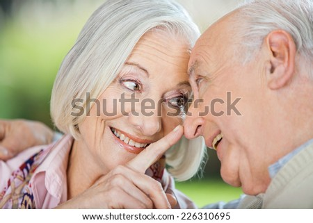 Loving senior woman touching man's nose at nursing home - stock photo