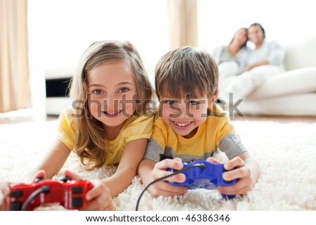 Loving siblings playing video game in the living room - stock photo