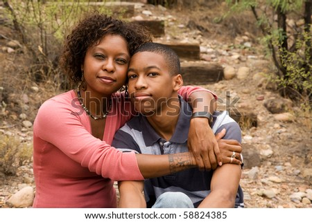 Loving single-mother hugging her handsome teenage son - stock photo