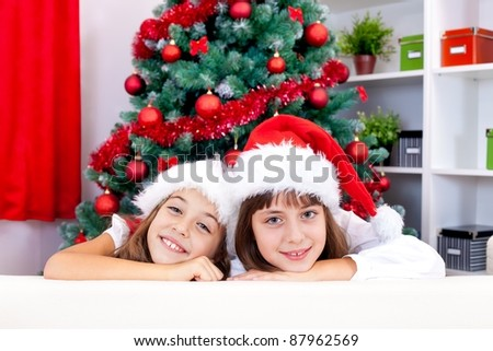 Loving sisters in santa hat near the Christmas tree