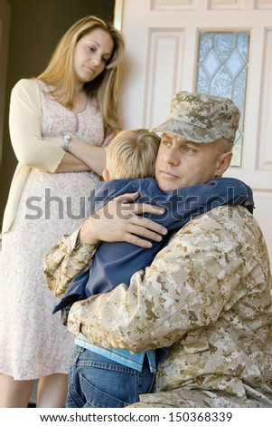Loving soldier embracing son before departing while mother looking at them - stock photo