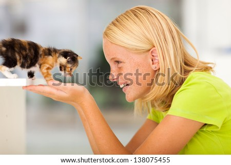 loving teen girl playing with pet kitten at home - stock photo