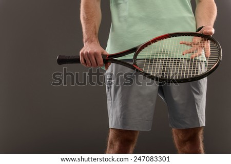 Loving tennis. Cropped image of young sportsman holding tennis racket against grey background - stock photo