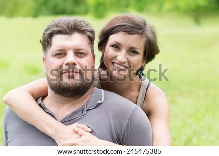 Loving woman embracing her lover in the park - stock photo