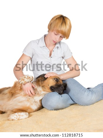Loving woman with her large gentle crossbreed dog lying with its head on her lap stroking it - stock photo
