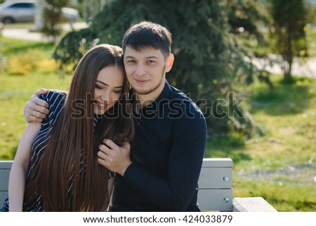 Loving young beautiful couple sitting on the bench hugging with copy space - stock photo