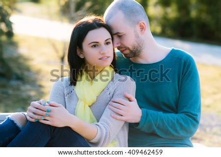 Loving young calm and serious couple boyfriend and girlfriend or husband with wife sitting on the bench in the park hug with copy space strong back light and lens flare cold toning - stock photo