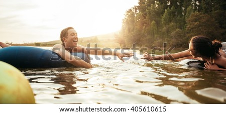Loving young couple about to hold hands while floating on inner tubes in lake. Young man and woman on an inflatable tube in water. - stock photo