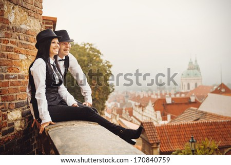Loving young couple are sitting in front of Prague roofs - stock photo