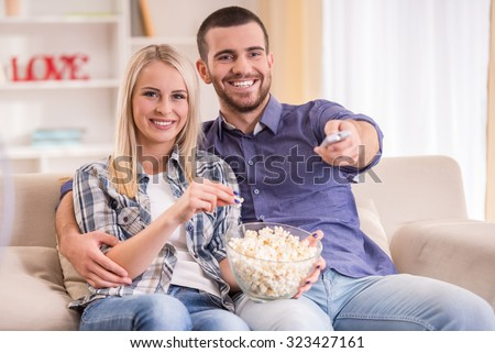 Loving young couple at home sitting on the couch, watch TV and eat popcorn - stock photo