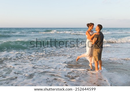 Loving young couple at the beach , in a late summer hazy day at dusk, wearing  a white dress and shorts, enjoying, going barefoot in the ocean water, getting wet, teasing and kissing one another. - stock photo