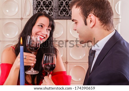 Loving young couple drinking red wine and smiling into each others eyes as they sit at a table in a restaurant enjoying a romantic date / Romantic young couple drinking red wine