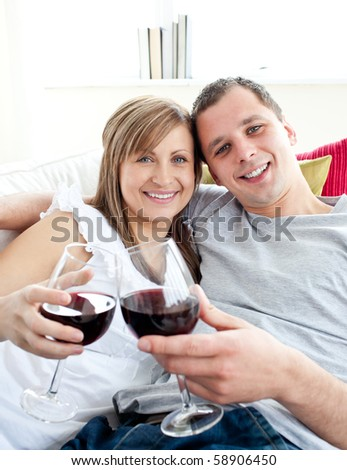 Loving young couple drinking wine sitting on a sofa in the living room
