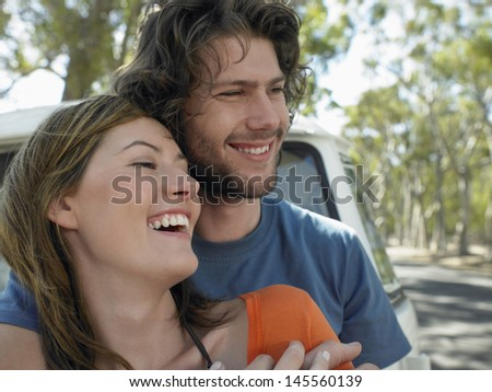 Loving young couple embracing in front of campervan during road trip - stock photo