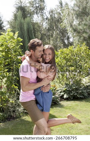 Loving young couple embracing in summer park - stock photo