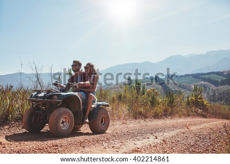 Loving young couple enjoying a quad bike ride in countryside. Couple riding on an ATV. - stock photo