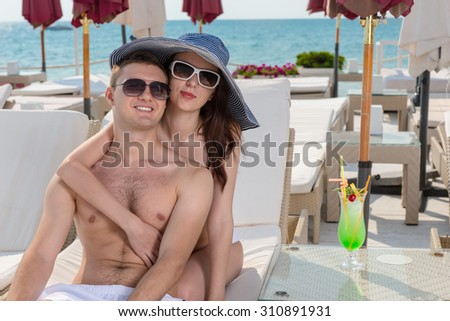 Loving young couple enjoying a summer vacation sitting relaxing in an intimate embrace at a tropical resort at the seaside on a recliner chair - stock photo
