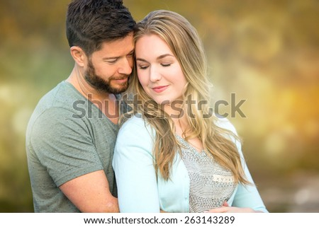Loving young couple holding each other outside - stock photo