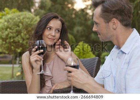 Loving young couple holding wine glasses in park - stock photo
