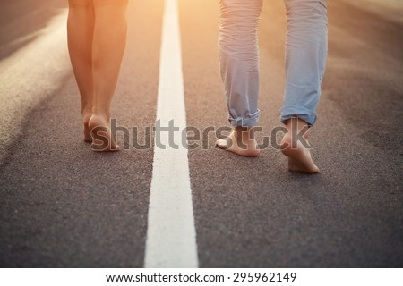 Loving young couple hugging and kissing. Two lovers barefoot on the road. - stock photo