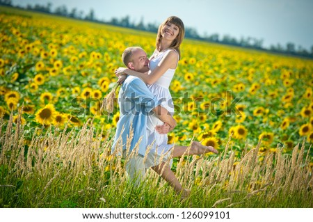 loving young couple in a field of sunflowers - stock photo