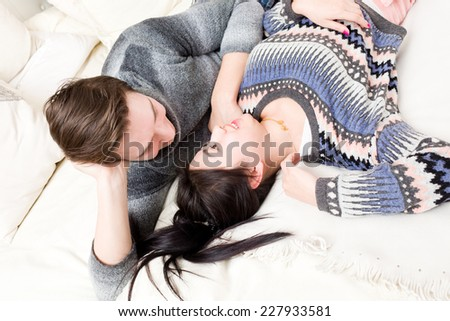 Loving young couple lying down on the bed, smiling and looking at each other - stock photo