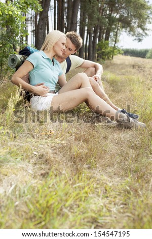 Loving young couple relaxing while hiking in forest
