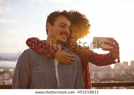 Loving young couple sharing a moment while taking a selfie to keep the memory alive with a city scape behind them