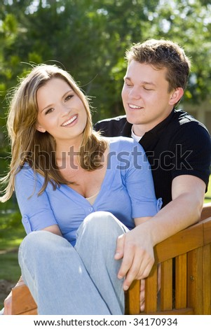 Loving young couple sitting on a bench - stock photo