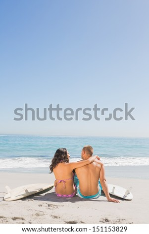 Loving young couple sitting on the beach with their surfboards