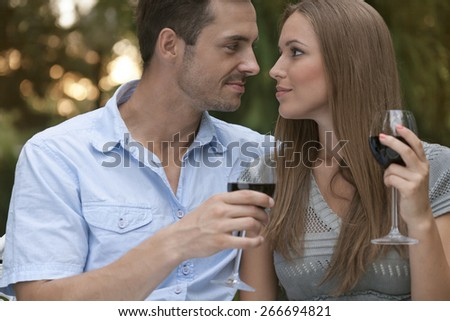 Loving young couple with red wine looking at each other in park - stock photo
