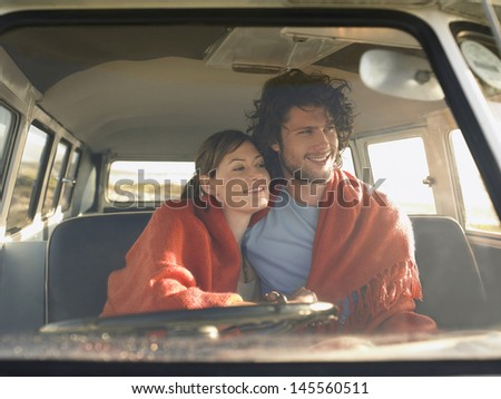 Loving young couple wrapped with blanket in front seat of campervan - stock photo
