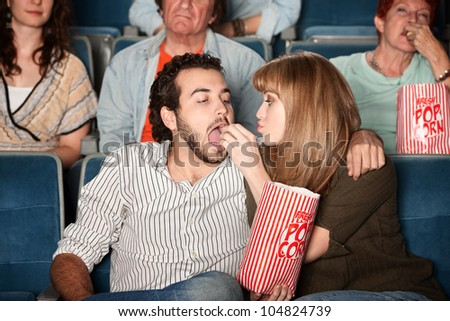 Loving young girlfriend feeds boyfriend popcorn in a theater - stock photo