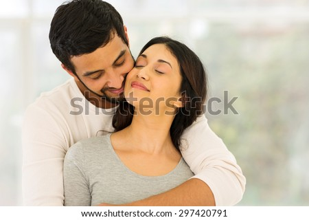loving young indian couple embracing at home  - stock photo