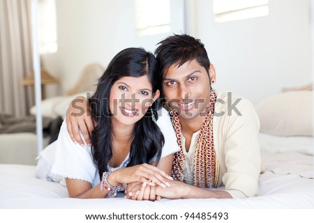loving young indian couple in traditional clothing and lying on bed