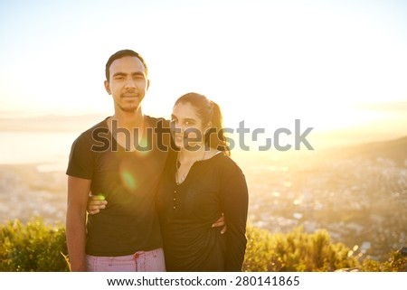 Loving young Indian couple posing outdoors in nature on a sunny morning with sun flare - stock photo