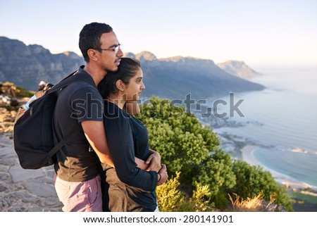 Loving young Indian couple taking in the view while on a mountain nature hike - stock photo