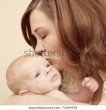 Loving young mother kisses her newborn son