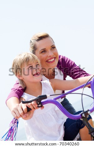 low angel view of happy mother teaching little girl how to ride a bicycle - stock photo