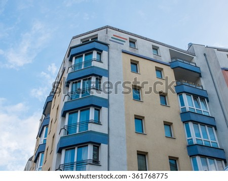 Low Angle Architectural Exterior View of Corner of Modern Colorful Low Rise Residential Building with Large Windows and Balconies with Blue Sky and Clouds in Background