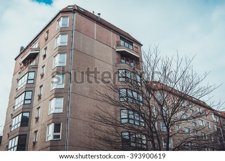 Low Angle Architectural Exterior View of Low Rise Residential Apartment Building with Bay Windows and Brown Stone Facade on Dreary Day with Bare Trees and Overcast Gray Sky - stock photo