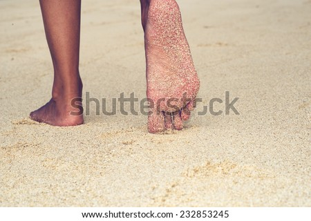 Low angle close up view of the bare feet of an Asian woman exploring a tropical beach walking away across the golden sand - stock photo