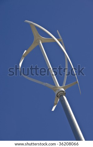 Low angle diagonal view of vertical axis wind turbine against a clear blue sky - stock photo