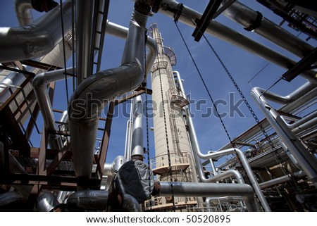 Low angle, exterior view of a tower at a gas compressor plant as seen through a variety of piping. Horizontal shot. - stock photo