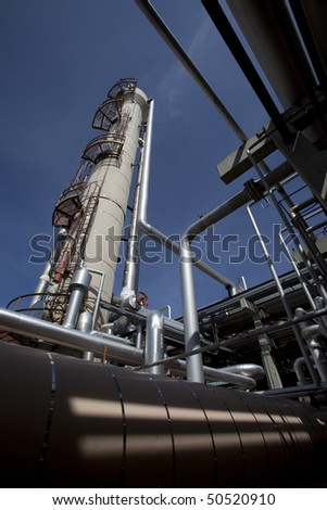Low angle, exterior view of a tower at a gas compressor plant with large pipes in the foreground. Vertical shot. - stock photo