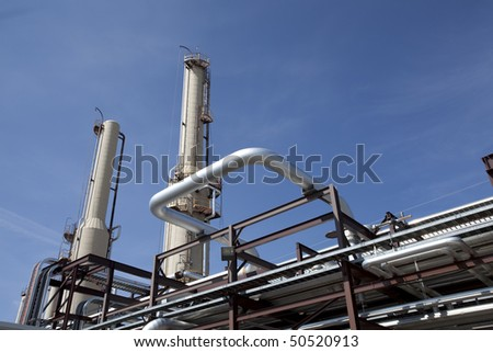 Low angle, exterior view of the piping at a gas compressor plant. Horizontal shot. - stock photo