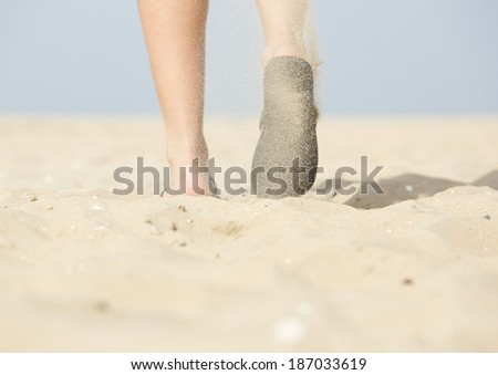 Low angle from behind view of woman walking with flip flops on beach - stock photo