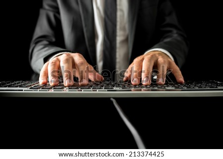 Low angle frontal view over the desk of a businessman typing on a computer keyboard with copyspace in the foreground. - stock photo